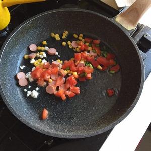 Предварительно порезанные овощи (помидор, перец, лук, кукуруза, если хотите можете добавить сосиски, куриное мясо) жарим до полуготовности.