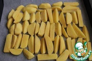 Картошку нарезать, выложить на противень, застеленный пергаментом, посолить и посыпать панировочными сухарями.